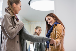 Young woman looking at friend wearing jacket in clothing storeの写真素材 [FYI03652386]