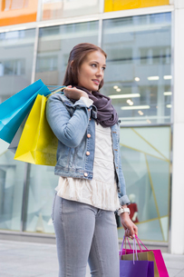 Young woman in casuals carrying shopping bags outdoorsの写真素材 [FYI03652414]