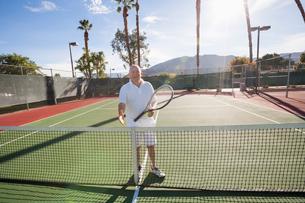 Portrait of senior tennis player offering handshake on courtの写真素材 [FYI03652437]