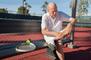 Senior male tennis player with leg pain sitting on bench at courtの写真素材 [FYI03652443]