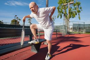 Senior male tennis player with back pain on courtの写真素材 [FYI03652446]