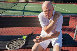 Senior male tennis player with shoulder pain sitting on bench at courtの写真素材 [FYI03652447]