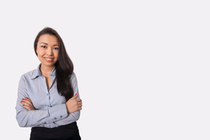 Portrait of confident businesswoman standing arms crossed against gray backgroundの写真素材 [FYI03652493]