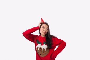 Woman wearing Christmas jumper and party hat against gray backgroundの写真素材 [FYI03652498]