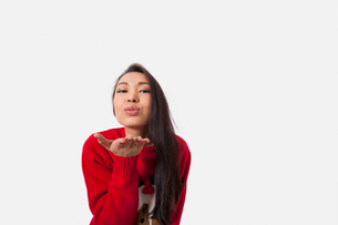 Portrait of woman in Christmas sweater blowing kiss over gray backgroundの写真素材 [FYI03652500]