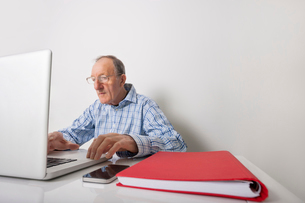 Senior businessman using laptop with book binder and cell phone on office deskの写真素材 [FYI03652505]