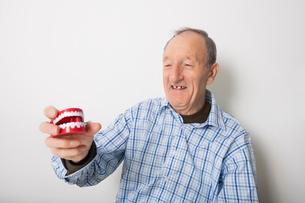 Happy senior man holding dentures against gray backgroundの写真素材 [FYI03652513]