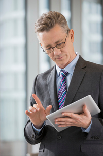 Businessman gesturing while using digital tablet in officeの写真素材 [FYI03652542]