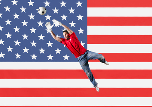 Football Goalkeeper saving shot in front of USA National Flagの写真素材 [FYI03652587]