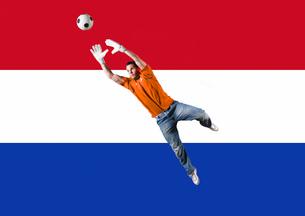 Football Goalkeeper saving shot in front of Dutch National Flagの写真素材 [FYI03652589]