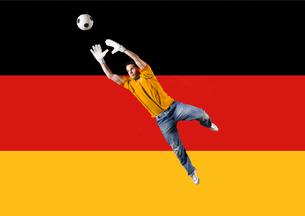 Football Goalkeeper saving shot in front of German National Flagの写真素材 [FYI03652590]
