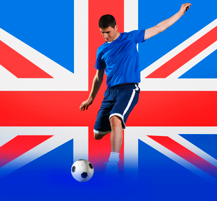 Football player shooting in front of Union Jack National Flagの写真素材 [FYI03652593]