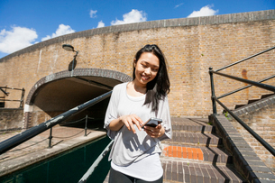 Smiling young woman using smart phone on stairsの写真素材 [FYI03652603]