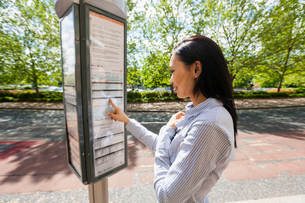 Side view of young businesswoman reading information sign on streetの写真素材 [FYI03652634]