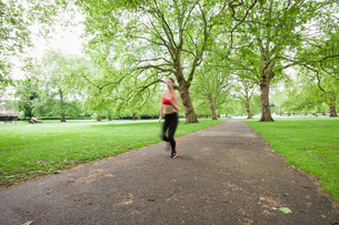 Blurred motion of woman jogging in parkの写真素材 [FYI03652635]