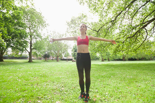Full length of young woman listening to music while exercising in parkの写真素材 [FYI03652642]
