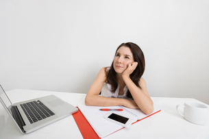 Thoughtful businesswoman with laptop and binder at desk in officeの写真素材 [FYI03652658]
