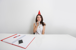 Portrait of happy businesswoman in party hat blowing horn at desk in officeの写真素材 [FYI03652661]