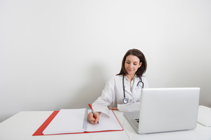 Female doctor writing on binder at desk in clinicの写真素材 [FYI03652664]