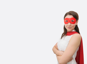 Portrait of confident businesswoman dressed as superhero standing arms crossed in officeの写真素材 [FYI03652665]