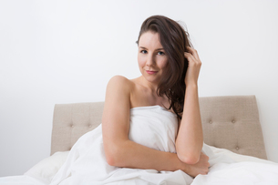 Portrait of sensuous woman covered with bedsheet in bedの写真素材 [FYI03652679]