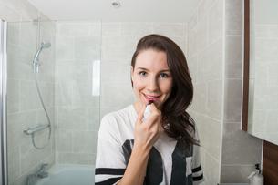 Portrait of young woman applying lipstick in bathroomの写真素材 [FYI03652684]