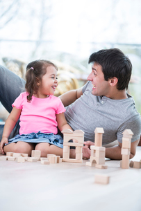 Cute girl teasing father while playing with wooden building blocks at homeの写真素材 [FYI03652689]