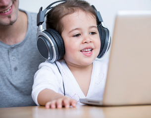 Little girl wearing headphones while looking at laptop with father at table in houseの写真素材 [FYI03652692]