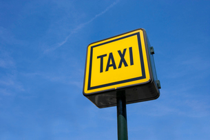 Low angle view of taxi sign against blue skyの写真素材 [FYI03652713]