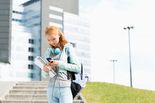 Young woman using smart phone at college campusの写真素材 [FYI03652799]