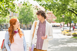 Young male and female college students talking while walking on footpathの写真素材 [FYI03652815]