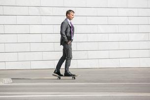 Businessman skateboarding on streetの写真素材 [FYI03652869]