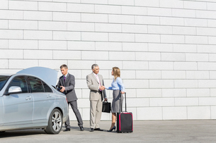 Businesspeople with luggage shaking hands outside car on streetの写真素材 [FYI03652873]