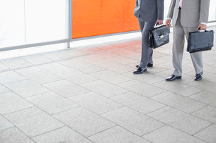 Low section of businessmen with briefcase walking in railroad stationの写真素材 [FYI03652898]