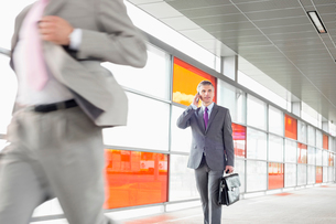 Middle aged businessman on call while walking in railroad stationの写真素材 [FYI03652900]