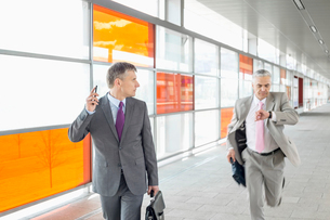 Middle aged businessman looking at colleague running in railroad stationの写真素材 [FYI03652901]