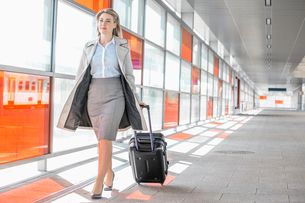 Full length of young businesswoman with luggage walking in railroad stationの写真素材 [FYI03652906]