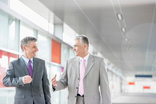 Happy middle aged businessmen talking while walking in railroad stationの写真素材 [FYI03652913]