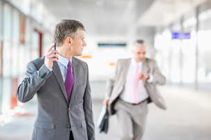 Middle aged businessman looking at colleague running in railroad stationの写真素材 [FYI03652915]