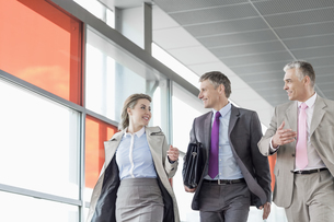 Businesspeople communicating while walking on railroad platformの写真素材 [FYI03652920]
