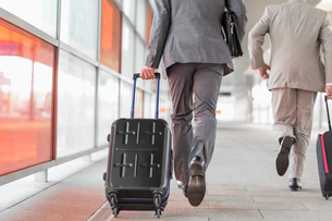 Rear view of businessmen with luggage running on railroad platformの写真素材 [FYI03652921]