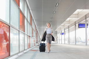 Full length of young businesswoman with luggage rushing in railroad stationの写真素材 [FYI03652924]