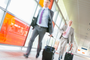 Middle aged businessmen with luggage rushing on railroad platformの写真素材 [FYI03652927]