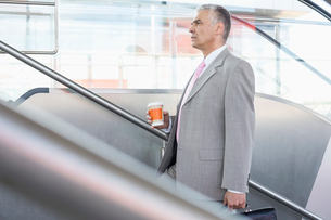 Side view of middle aged businessman with coffee cup walking up stairs in railroad stationの写真素材 [FYI03652937]