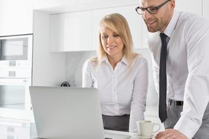 Happy mid adult business couple using laptop at kitchen counterの写真素材 [FYI03652949]