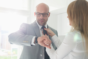 Mid adult businessman checking wristwatch while woman adjusting his tie at homeの写真素材 [FYI03652954]