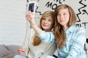 Cute sisters taking photos with smart phone at homeの写真素材 [FYI03652966]