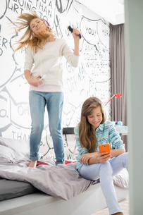 Sisters having leisure time in bedroomの写真素材 [FYI03652972]