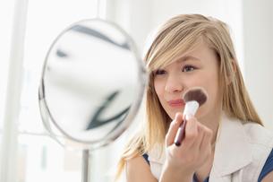 Girl applying makeup in front of mirror at homeの写真素材 [FYI03652981]