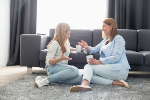 Happy mother and daughter talking while having coffee in living roomの写真素材 [FYI03652990]